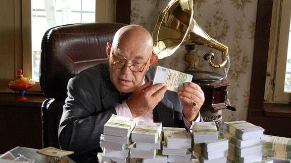 Spielzeugfabrikant Wamske (Hans-Martin Stier) beim Geld zählen.