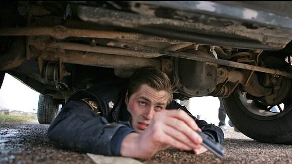 Pontus (Sverrir Gudnason) hat sich unter dem Polizeiwagen versteckt und filmt einen Raubüberfall mit dem Handy