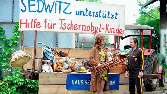Ralle Pietzsch (Thorsten Merten) und Astrid Hillebrand (Judith Richter) stehen vor einem Taktor mit Spenden für Tschernobyl-Kinder im Anhänger.