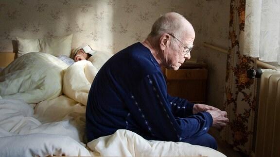 Ein älterer Mann erwacht neben seiner Ehefrau, die im Schlaf gestorben ist