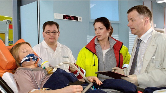 Britta Hanke (Daniela Preuß, li.) wird nach einem Autounfall von Dr. Elena Eichhorn (Cheryl Shepard, 2.v.re.) mit dem Notarztwagen in die Sachsenklinik gebracht. Dr. Heilmann (Thomas Rühmann, re.), der Britta gleich erkennt, und Pfleger Brenner (Michael Trischan, 2.v.li.) nehmen sie in Empfang.