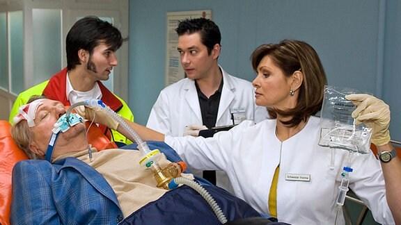 Ein Rettungssanitäter (Roman Petermann, li.) bringt Dr. Gerd Behringer (Reiner Schöne, liegend) nach einem Autounfall in die Sachsenklinik. Dr. Brentano (Thomas Koch, mi.) und Schwester Yvonne (Maren Gilzer, re.) nehmen ihn bewusstlos auf.