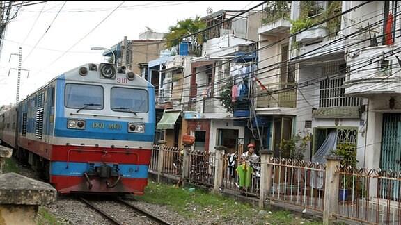 """1 700 Kilometer lang ist die Strecke von Hanoi nach Ho-Chi-Minh-Stadt. 40 Stunden braucht der Zug dafür. Die Vietnamesen nennen ihn """"Wiedervereinigungsexpress"""". Leben am Bahngleis."""