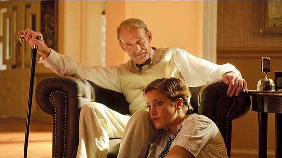 Ein älterer Mann sitzt auf einem ledernen Sessel. In seiner Hand hält er einen hölzernen Gehstock. Zu seinen Füßen sitzt eine Frau, die sorgenvoll zur Seite schaut.