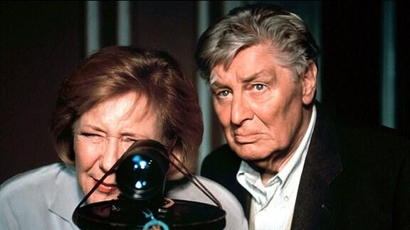 Der pensionierte Bauunternehmer Arno Adelmann (Günter Pfitzmann) und seine Haushälterin Nancy (Veronika Fitz) beobachten mit dem Nachtsichtgerät, wie die Tochter und der Schwiegersohn das Haus observieren.