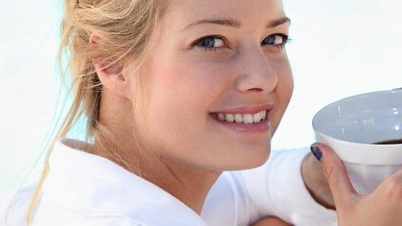 eine junge Frau hält eine Schale Kaffee