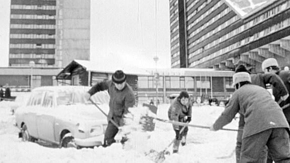 Menschen schippen Schnee vor einem Hotel
