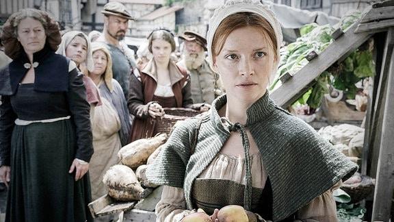 Eine Frau in mittelalterlicher Kleidung auf dem Markt. Hinter ihr Marktbesucher, die sie neugierig beäugen.