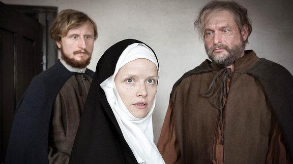 Eine Frau in Nonnentracht, hinter ihr zwei Männer