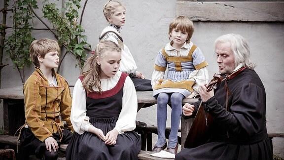Mittelalterlich gekleidete Kinder mit einem Mann beim singen.