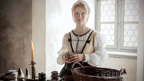 Eine Frau in mittelalterlicher Kleidung vor einem Fenster. Sie hält einen kleinen Behälter in der Hand.