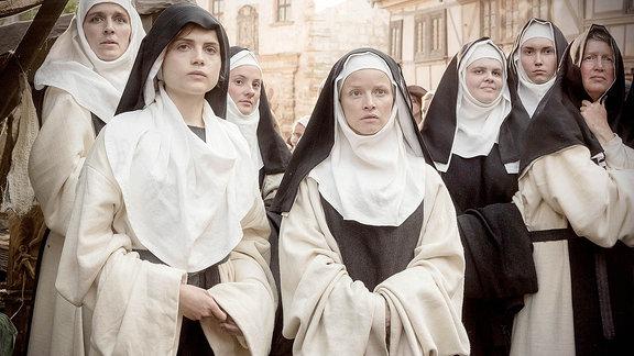 Eine Gruppe von Frauen in Nonnentracht blicken unsicher.
