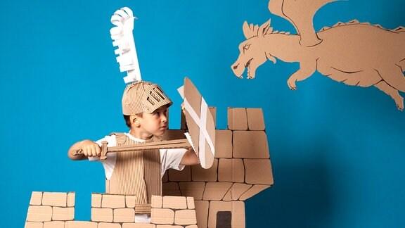 Ein Kind spielt Ritter mit Helm, Schild, Schwert und Burg aus Pappe