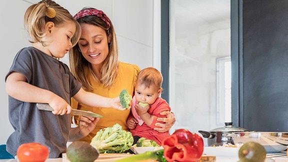 Eine Mutter schneidet zusammen mit zwei Kindern Gemüse