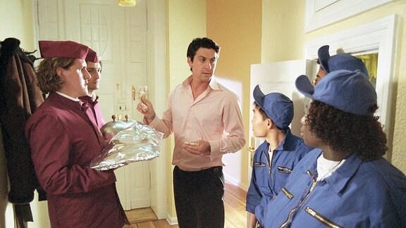 Ein junger Mann in eleganter Kleidung drückt zwei Männern, Angestellte eines Gastro-Service, und drei Reinigungskräften ein paar Geldscheine in die Hand.