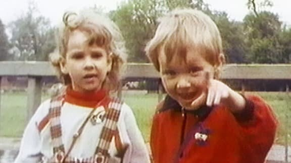 Ein Junge und ein Mädchen blicken in die Kamera. Der Junge zeigt mit dem Finger auf die Kamera und lacht.