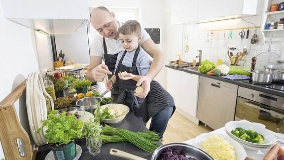 Vater und Sohn kochen gemeinsam viel frisches Gemüse.