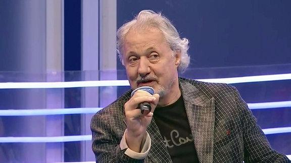Ein Mann mit grauen Haaren spricht auf der Buchmesse in ein Mikrofon.