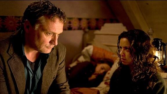 Lutz spricht mit Eva. Im Hintergrund schläft seine Tochter Lea.