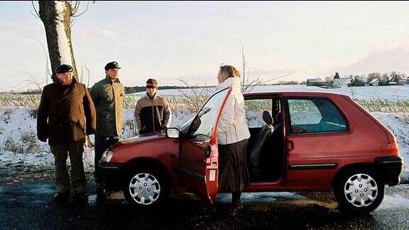 Krause (Horst Krause, li.) und Forstarbeiter Liebmann (Dominique Horwitz) versuchen das Auto wieder flottzukriegen, mit dem Marie Dost (Gabriela Maria Schmeide) und ihr Sohn Fabian (Enno Trebs) kurz vor Schönhorst liegen geblieben sind.