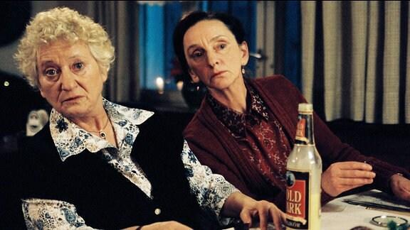 Krauses Schwestern Elsa und Meta sitzen vor einer Flasche Eierlikör.