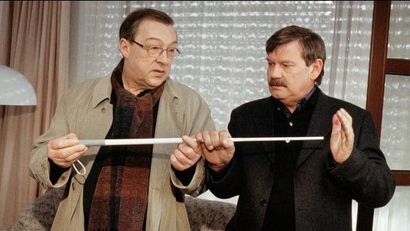 Die Kommissare Schmücke (Jaecki Schwarz, li.) und Schneider (Wolfgang Winkler) wundern sich, warum der blinde Masseur seinen Blindenstock zurückgelassen hat.