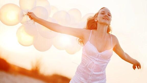 Eine glücksstrahlende junge Frau mit Luftballons.