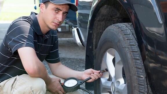 Ein Mann überprüft den Luftdruck an seinen Autoreifen