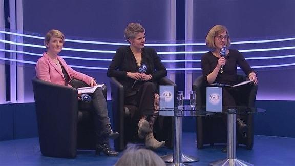 Drei Frauen sitzen auf einer Bühne.