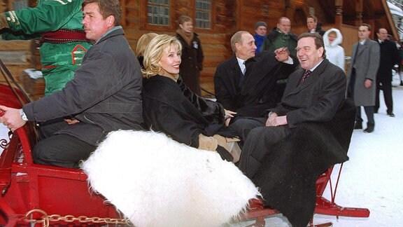 Lachend und winkend fahren der russische Präsident Wladimir Putin, Bundeskanzler Gerhard Schröder (r) und dessen Frau Doris Schröder-Köpf am 7.1.2001 in Kolomenskoje, der früheren Sommerresidenz der Zaren in Moskau, in der russischen «Troika», einem von drei Pferden gezogenen Schlitten.