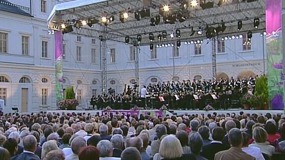 Ein Chor steht zusammen mit Musikern eines Orchesters auf der Bühne.