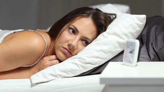 Eine schalflose Frau schaut auf Ihren Wecker nachts im Bett