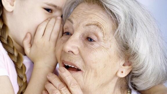 Ein kleines Mädchen flüstert der Oma etwas ins Ohr.
