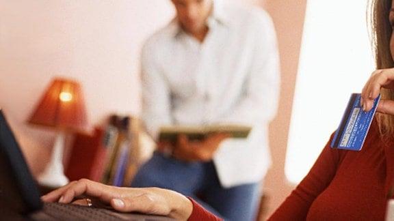 Eine junge Frau schaut in ihren Laptop und hält ihre Kreditkarte in der Hand.