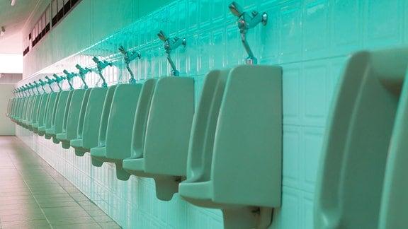 Porzellan-Urinale hängen in einer Reihe an der Wand einer öffentlichen Toilette