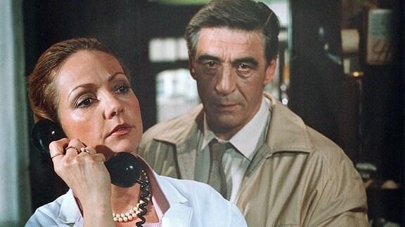 Oberleutnant Hübner (Jürgen Frohriep) steht hinter der telefonierenden Drogistin (Regina Beyer).