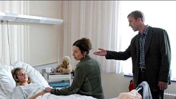 Anja liegt im Krankenhausbett, ihre Eltern stehen daneben.