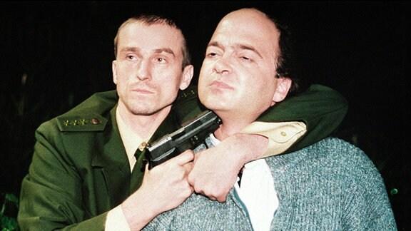 Polizist bedroht einen Mann mit seiner Waffe