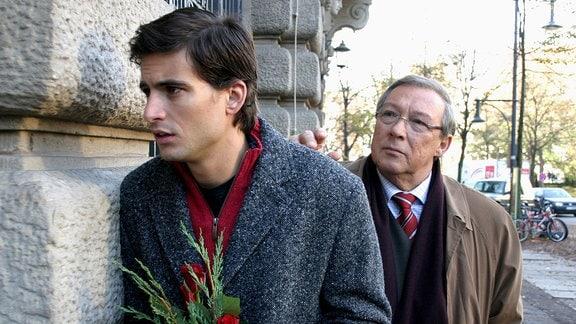 Ein Mann mit einem Strauß Rosen in der Hand ist gerade dabei, durch den Hintereingang zu treten, während ihm Schmücke von hinten auf die Schulter tippt.