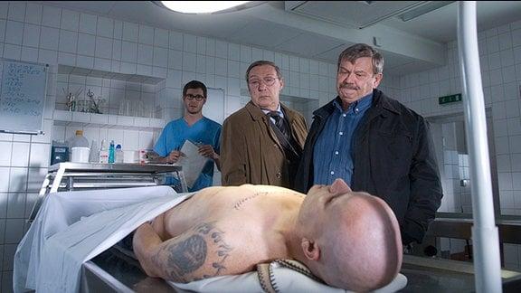 Dr. Stabroth (Jochen Schropp, im Hintergrund) erklärt Schmücke (Jaecki Schwarz, Mitte) und Schneider (Wolfgang Winkler, rechts) nach der Obduktion von Frank Ziehrer, dass ein Fremdverschulden nicht ausgeschlossen werden kann