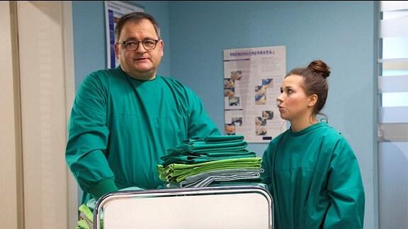 Pfleger Hans-Peter Brenner (Michael Trischan) ist genervt: Die neue Schwester Julia (Sarah Tkotsch), die heute unter seiner Obhut steht, hat die Patientenbetten nicht ordentlich bezogen.