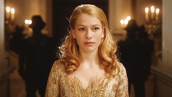 Eine junge Frau mit goldenen Haaren trägt ein goldenes Kleid