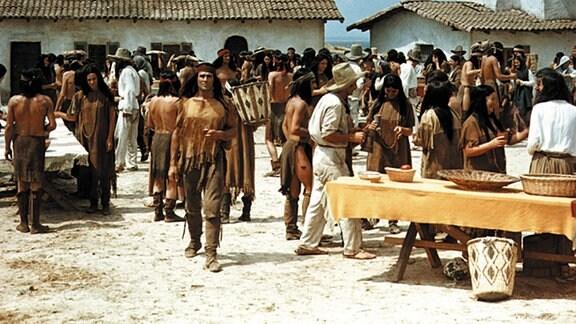 Die Mimbreno-Apachen haben einer mexikanischen Kupferminengesellschaft die Schürfrechte auf Indianergebiet vertraglich gesichert. Die Gesellschaft garantiert ihrerseits den Lebensunterhalt der Indianer, für die es kaum noch ausreichend Jagdgebiete gibt. Die Übergabe der Lebensmittel wird zum gemeinsamen Fest und Höhepunkt des Jahres. Doch der junge Häuptling Ulzana (Gojko Mitic, vorne Mitte) ist misstrauisch.