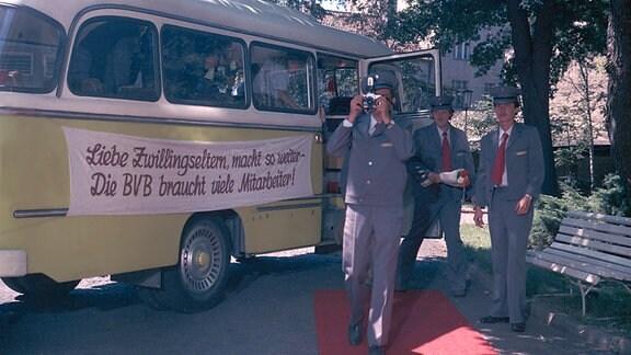 Maxis Arbeitskollegen holen die frischgebackene Mutter von Zwillingen standesgemäß mit Bus und rotem Teppich vom Krankenhaus ab