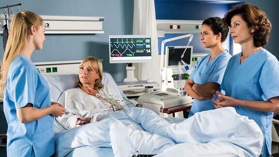 Nach Simones (Katharina Abt, 2.v.l.) Zusammenbruch vermuten die Ärzte eine vererbte Herzkrankheit. Julia Berger (Mirka Pigulla, l.), Dr. Leyla Sherbaz (Sanam Afrashteh, 2.v.r.) und Prof. Karin Patzelt (Marijam Agischewa, r.) erklären der Patientin, wie es jetzt weitergehen soll