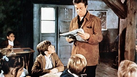 Peter Bach (Peter Alexander, stehend), zweifacher Doktor, ist versehentlich als Lehrer an der Zwergschule von Tuttelbach gelandet, fühlt sich aber mit seinem Neffen Jan (Heintje, 4. v. li.) sehr wohl dort.