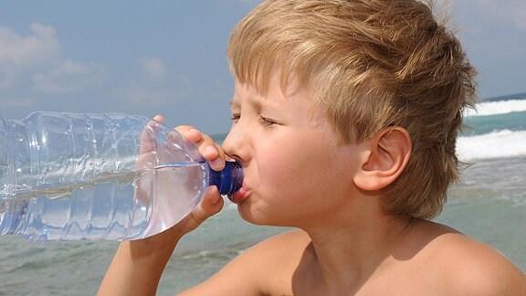 Ein Junge trinkt an einem Strand Wasser aus einer Flasche.