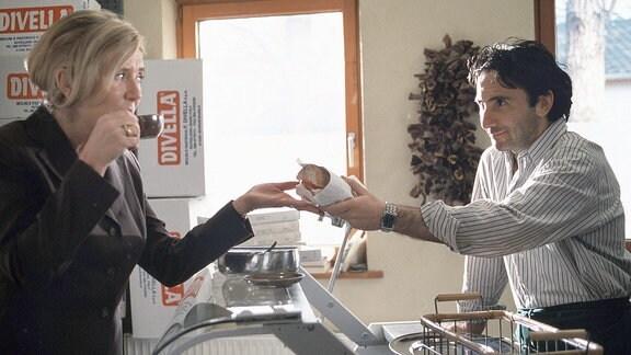 Enrico Aleramo (Bruno Maccallini) reicht der gestressten Barbara Seeberg (Jutta Speidel) einen in Papier gewickelten Snack über die Theke seines kleinen Bistros.