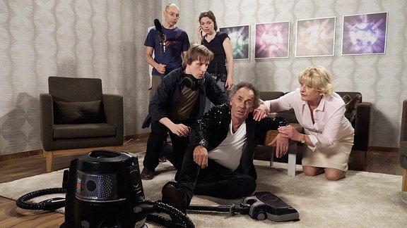 Ein älterer Mann sitzt auf dem Boden neben einem Staubsauger. Eine Frau und ein Filmteam knien besorgt neben ihm.
