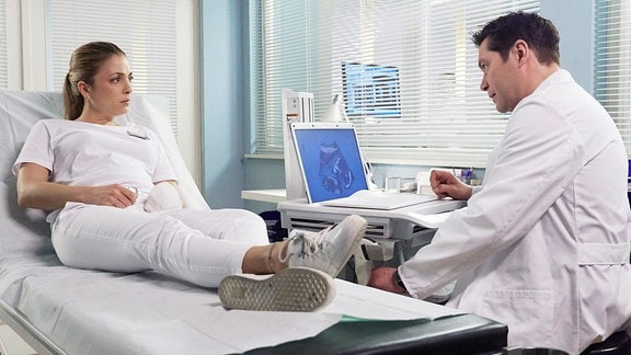 Eine Krankenschwester sitzt auf einer Liege. Sie sieht einen Arzt an, der neben ihr an einem Bildschirm sitzt.
